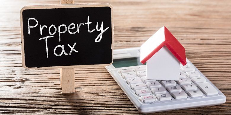 picture of a house and calculator with a property tax sign