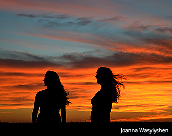 Picture of the silhouette of two people with the sunset in the background